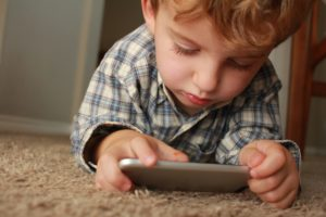 Boy playing games on a mobile phone