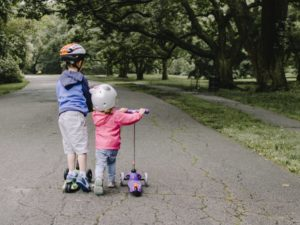 Children riding scooters wearing helmets for safety