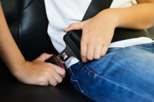 Child buckling his seat belt for summer safety