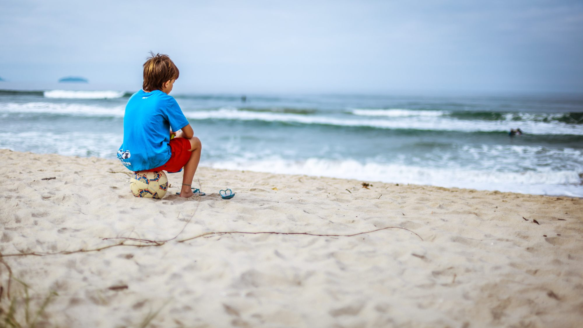 Child at the beach for summer break sitting on a soccer ball
